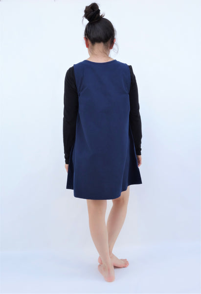A woman standing and wearing a cat-themed, cotton, dark blue shirt/mini A-line dress/top/tunic, back view