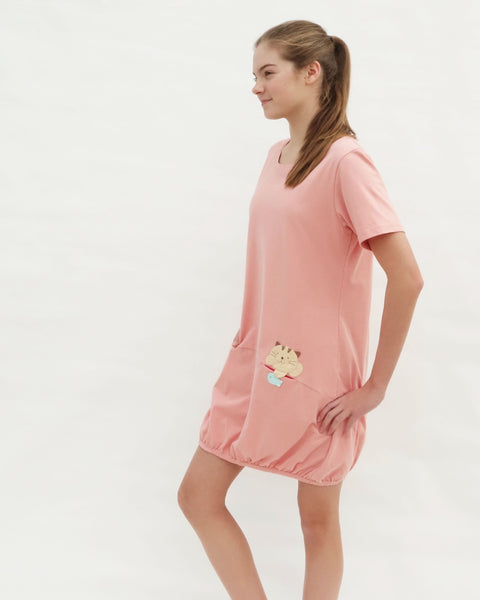 Woman wearing cat t-shirt dress in pink with cat appliqué,  embroidery, front pockets, round neck opening, short sleeves, in close-up side view.