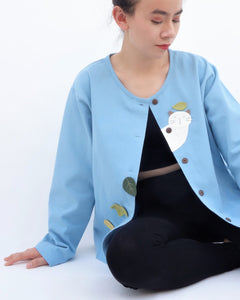 Woman sitting and wearing a blue cotton cat jacket with appliqué cat and leaves falling in the front. The jacket has buttons in the front.
