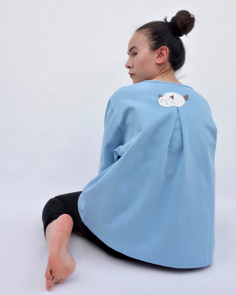 Woman sitting and wearing a blue cotton cat jacket with an appliqué cat sleeping on the back. The jacket has a pleat in the back. The woman is looking over her shoulder.