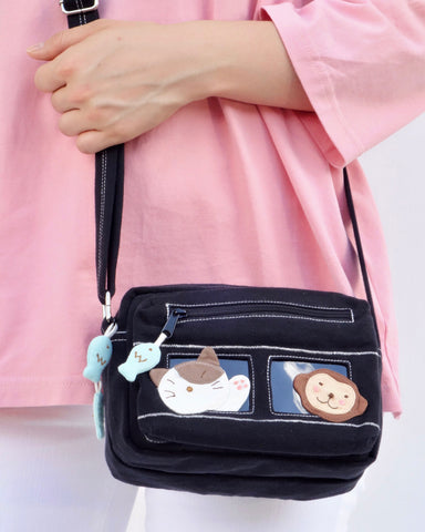 Close up of a woman holding a black cat-themed crossbody purse. There are blue fish charms on the zippers and two rectangular PVC windows with a cat and a monkey on the front.