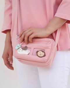 Close up of a woman holding a pink cat-themed crossbody purse. There are blue fish charms on the zippers and two rectangular PVC windows with a cat and a monkey on the front.