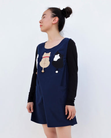 A woman standing and wearing a cat-themed, cotton, dark blue shirt/mini A-line dress/top/tunic with three appliqué cats on the front