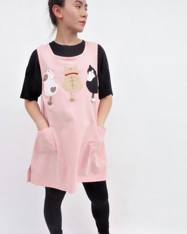 A woman standing and wearing a cat-themed, cotton, pink shirt/mini A-line dress/top/tunic with three appliqué cats on the front