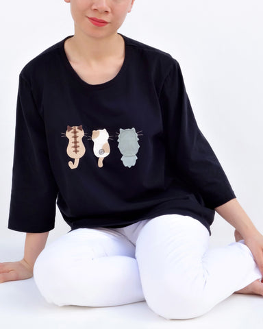 A woman is sitting casually and wearing a black cotton cat-themed shirt with 3 appliqué cats in the front, backs facing. The shirt has three quarter sleeves and a rounded neck.