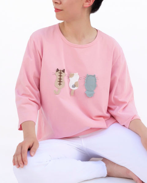 A woman is sitting casually and wearing a pink cotton cat-themed shirt with 3 appliqué cats in the front, backs facing. The shirt has three quarter sleeves and a rounded neck.