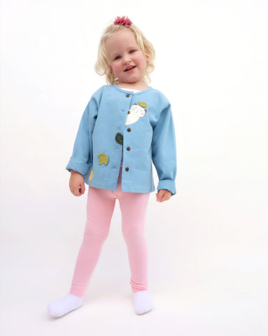A girl standing, smiling, and wearing a blue relaxed-fit cotton cat jacket with an appliqué peekaboo cat and falling leaves in the front. There are buttons on the jacket.