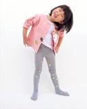 A playful girl standing, smiling, and wearing a pink relaxed-fit cotton cat jacket with an appliqué peekaboo cat and falling leaves in the front. There are buttons on the jacket.