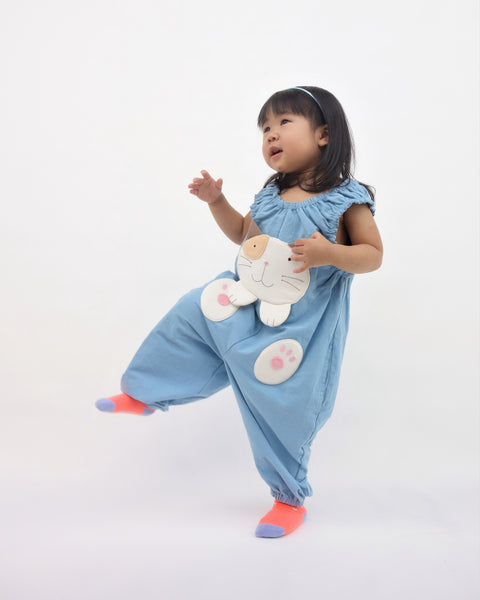 Girl pouncing in blue, cat-themed jumper with large, soft cat face pocket and cat paws in the front, two little fish friends swim on the back, sewn appliqué, embroidery details and side pockets in front view.