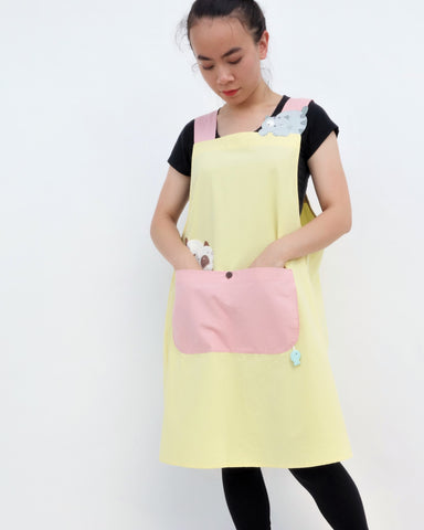Woman wearing pink and yellow color-blocked apron with cat appliqué, large front pocket, in front close-up view.