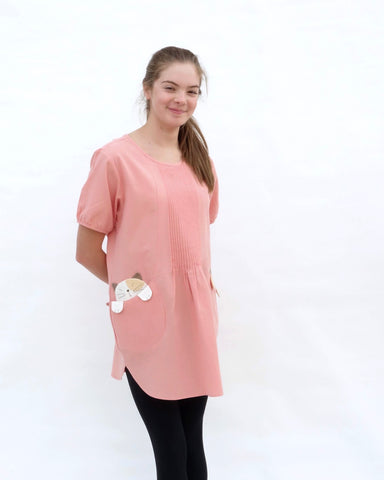 A woman standing, wearing a pink cotton cat-themed tunic dress for women with two cats/kittens on the pockets and black leggings underneath. The tunic dress has puffed sleeves and slits on the side.