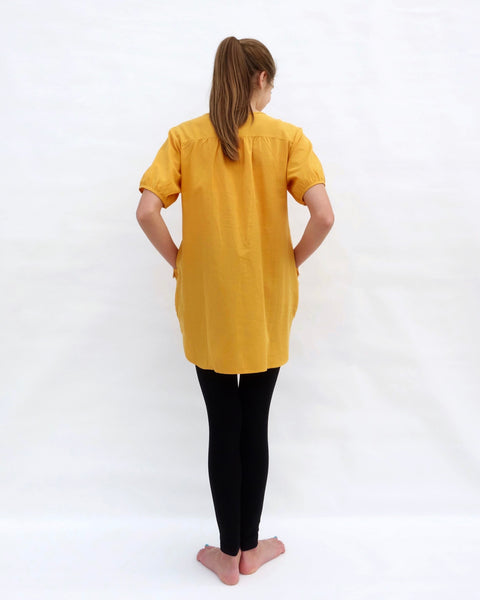 A woman standing, wearing a yellow cotton cat-themed tunic dress for women with black leggings underneath, back facing. The tunic dress has puffed sleeves and slits on the side.