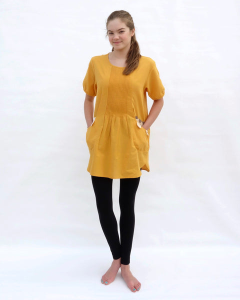 A woman with hands in the pockets, wearing a yellow cotton cat-themed tunic dress for women with two cats/kittens on the pockets and black leggings underneath. The tunic dress has puffed sleeves and slits on the side.