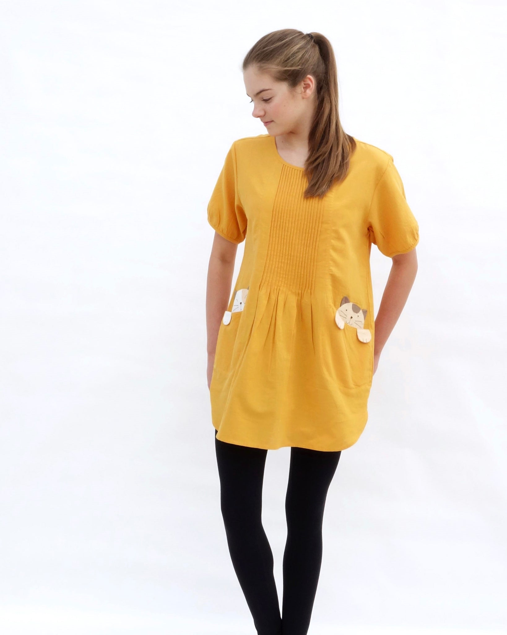 A woman with hands on the sides, wearing a yellow cotton cat-themed tunic dress for women with two cats/kittens on the pockets and black leggings underneath. The tunic dress has puffed sleeves and slits on the side.