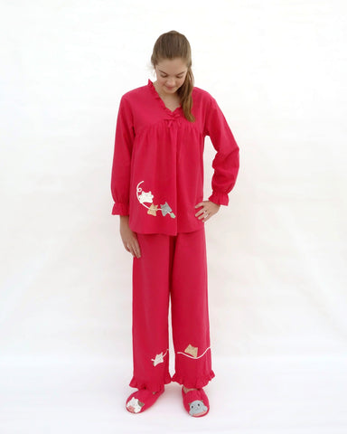Women wearing red pajamas with cat appliqué, embroidery details, and matching slippers in front view.