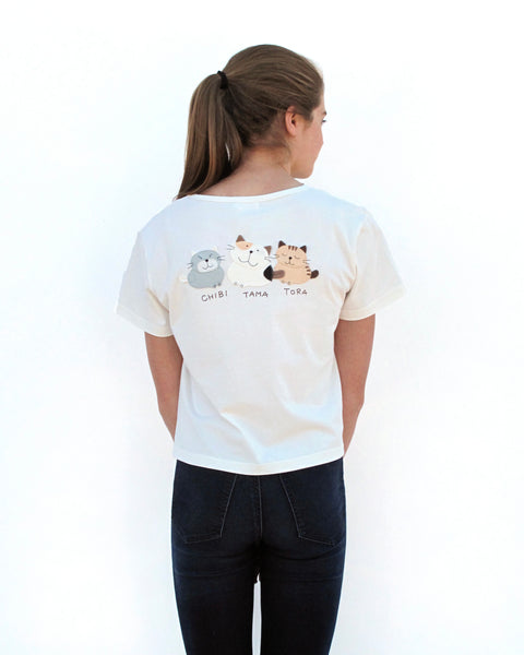 Woman wearing Cat Crop Top in white with three cat appliqué, embroidery details, V-neck and short sleeves in close-up back view.
