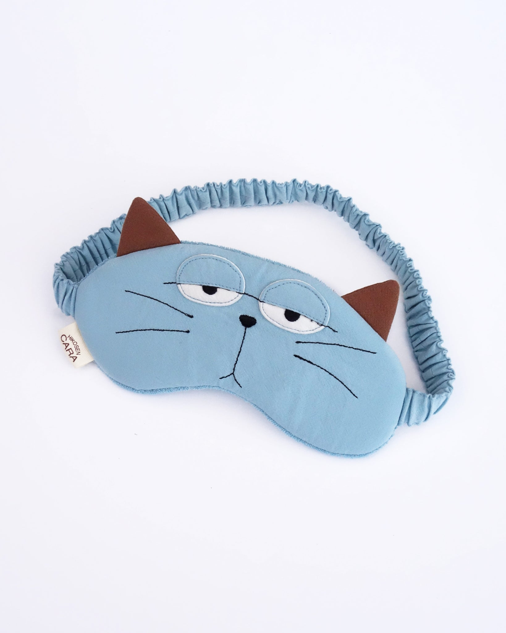 Cat eye mask in blue color with appliqué, embroidery, 3D cat ears, elastic strap, foam-padding, in front view.