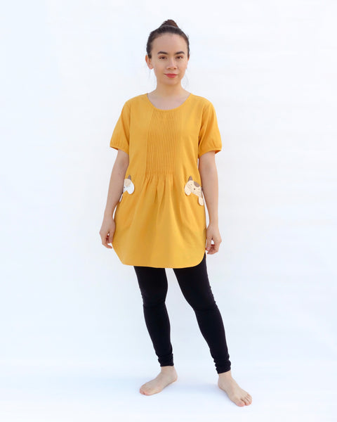 A woman with hands at her sides, wearing a yellow cotton cat-themed tunic dress for women with two cats/kittens on the pockets and black leggings underneath. The tunic dress has puffed sleeves and slits on the side.