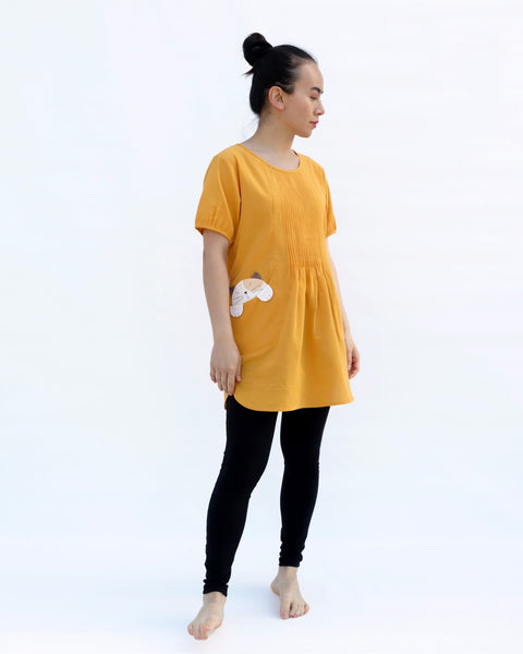 A woman with hands at her sides, wearing a yellow cotton cat-themed tunic dress for women with two cats/kittens on the pockets and black leggings underneath, side view. The tunic dress has puffed sleeves and slits on the side.