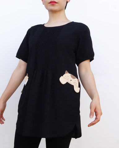 Woman wearing a black cotton cat-themed tunic dress for women with two cats/kittens on the pockets. The tunic dress has puffed sleeves and slits on the side.