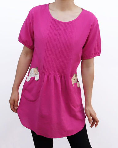 Woman wearing a hot pink/fuchsia cotton cat-themed tunic dress for women with two cats/kittens on the pockets. The tunic dress has puffed sleeves and slits on the side.