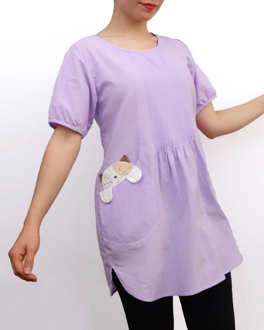 Woman wearing a lilac purple cotton cat-themed tunic dress for women with two cats/kittens on the pockets. The tunic dress has puffed sleeves and slits on the side.