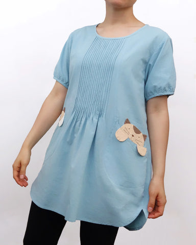 Woman wearing a sky blue cotton cat-themed tunic dress for women with two cats/kittens on the pockets and black tights leggings underneath. The tunic dress has puffed sleeves and slits on the side.