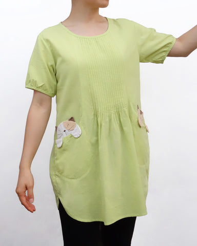 Woman wearing a light green cotton cat-themed tunic dress for women with two cats/kittens on the pockets and black tights leggings underneath. The tunic dress has puffed sleeves and slits on the side.