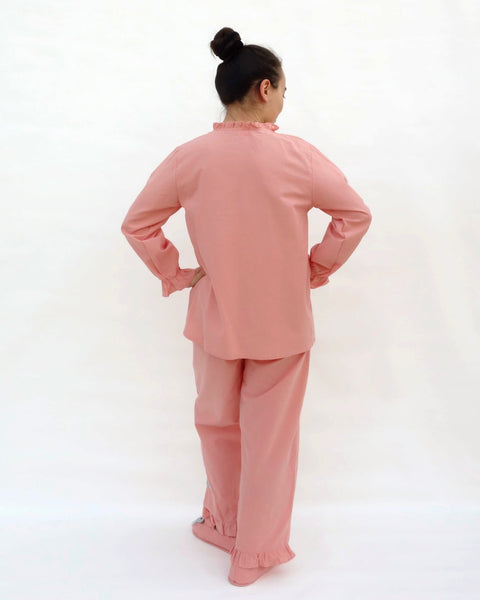 Women wearing pink pajamas with cat appliqué, embroidery details, and matching slippers in back view.