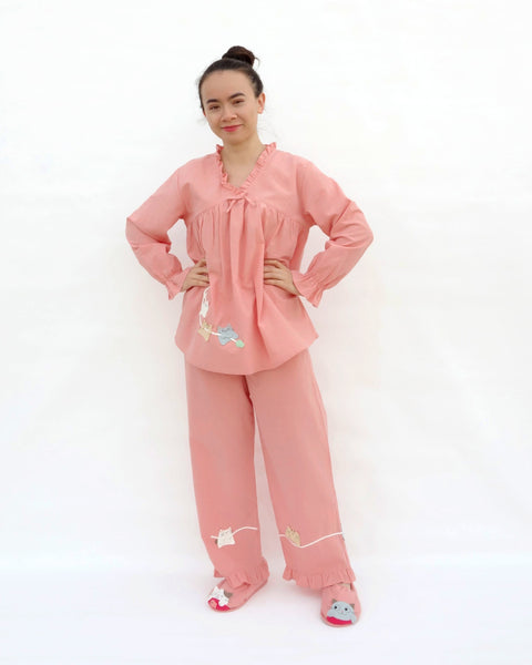 Women wearing pink pajamas with cat appliqué, embroidery details, and matching slippers in front view.