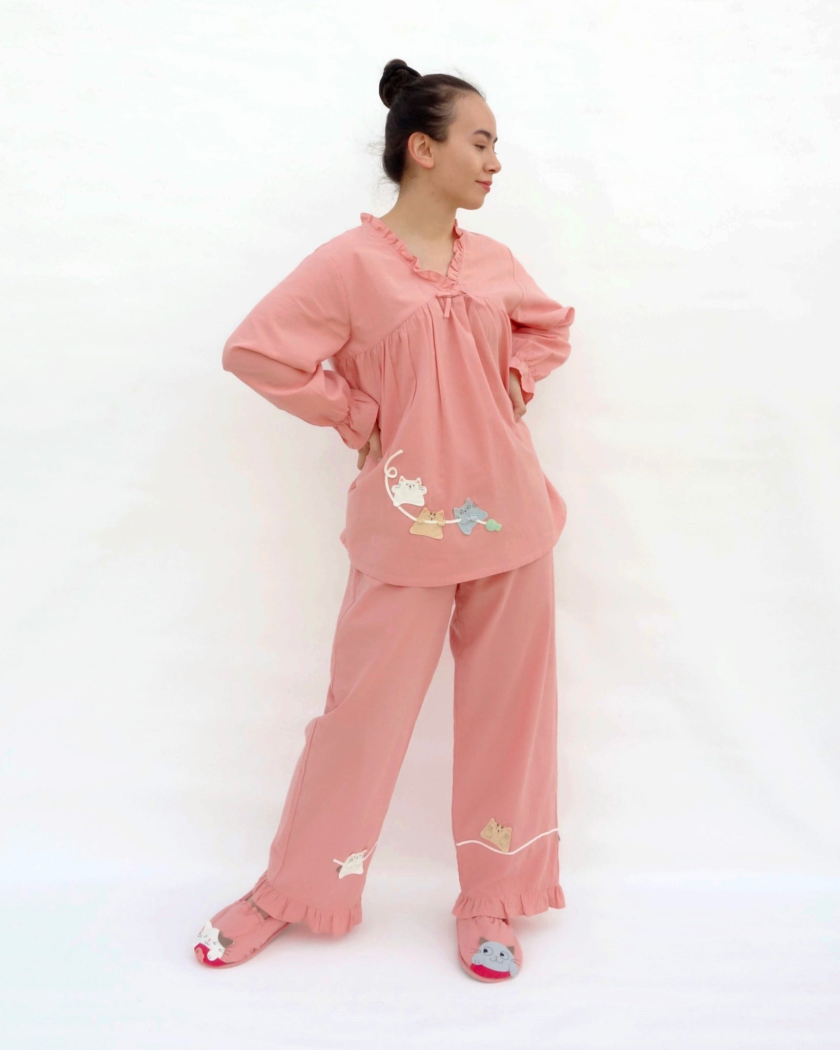 Women wearing pink pajamas with cat appliqué, embroidery details, and matching slippers in 3/4 view.