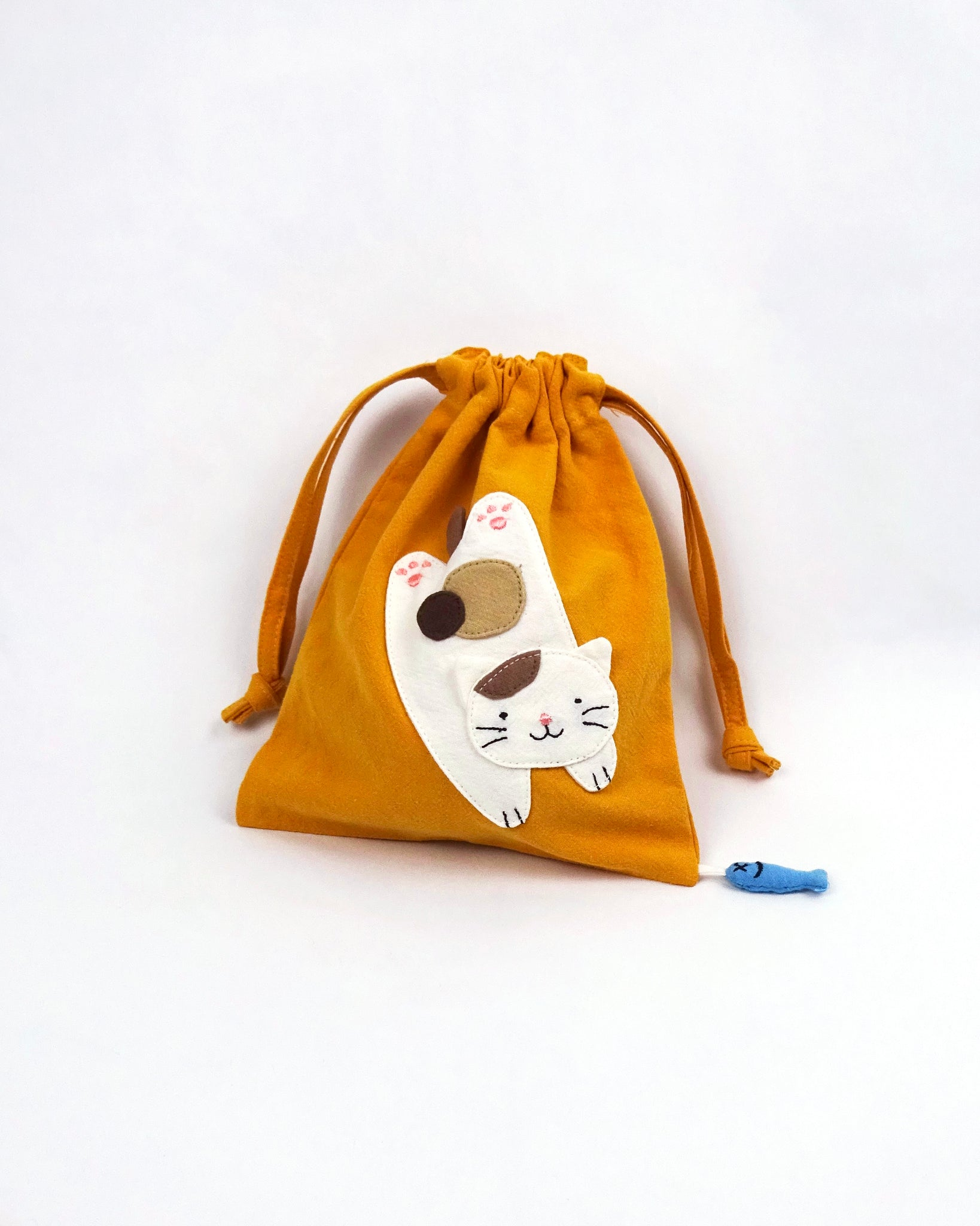Cat Pouch in golden yellow with cat appliqué, embroidery detail, two-sided drawstring enclosure, small blue fish hanging at the bottom right corner.