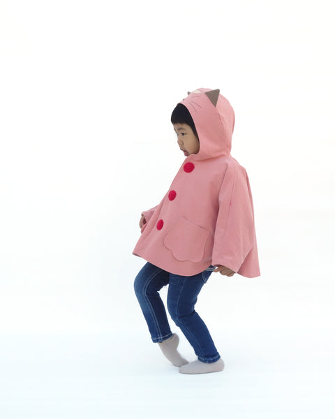 Toddler girl wearing pink kitten cape coat jacket with cat ears and face on the hood, cat paw pockets, and bright red buttons in side view.