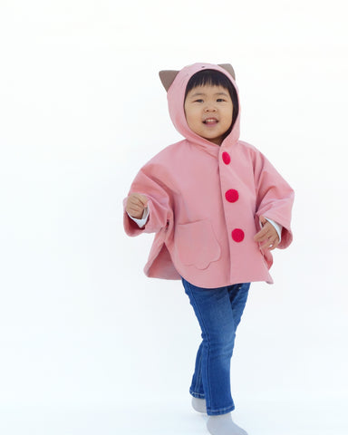 Cute girl smiling, walking forward to viewer, wearing a pink, kitten cape coat with appliqué and embroidered cat-like details on the hood and the back, two paw-shaped pockets on the front, contrasting hot-pink buttons are padded, and a cozy hood with cat ears sticking out.