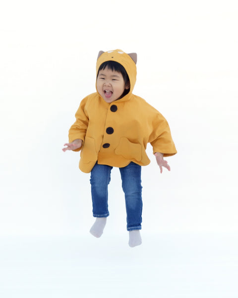 Toddler girl in golden yellow kitten cape coat jacket with cat ears and face on the hood, cat paw pockets, and buttons in the front