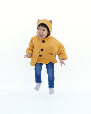 Cute girl jumping up with her fingers spread outward, wearing a yellow, kitten cape coat with appliqué and embroidered cat-like details on the hood, two paw-shaped pockets on the front, contrasting dark brown buttons are padded, and a cozy hood with cat ears sticking out.