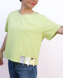 Women wearing a Cat Crop Top in green with bottom hem at the waist, three-cat appliqué on the front, one cat appliqué on the back, embroidery details, crew neck, and short sleeves in front close-up view.