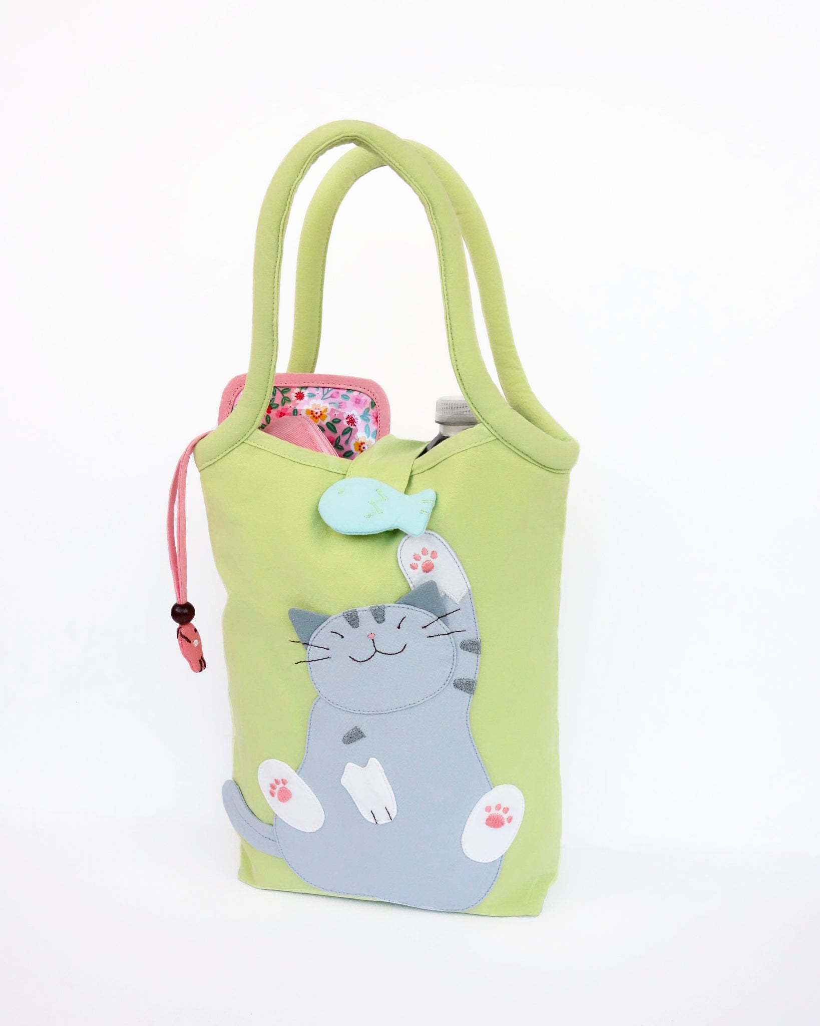 Cat Bottle-Tote in green with cotton interior, nylon lining, cat appliqué, embroidery detail, large main compartment, Velcro flap closure, sturdy double padded handles, squared off bottom for holding books, wallet, water bottle, pencil pouch, or umbrella.
