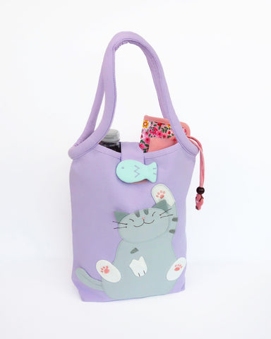 Cat Bottle-Tote in lilac with cotton interior, nylon lining, cat appliqué, embroidery detail, large main compartment, Velcro flap closure, sturdy double padded handles, squared off bottom for holding books, wallet, water bottle, pencil pouch, or umbrella.