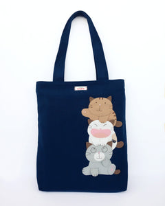 A navy blue cat-themed canvas tote bag with three appliqué cats playfully stacked on top of each other