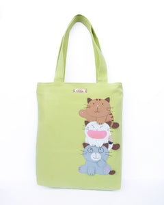 A light/spring green cat-themed canvas tote bag with three appliqué cats playfully stacked on top of each other