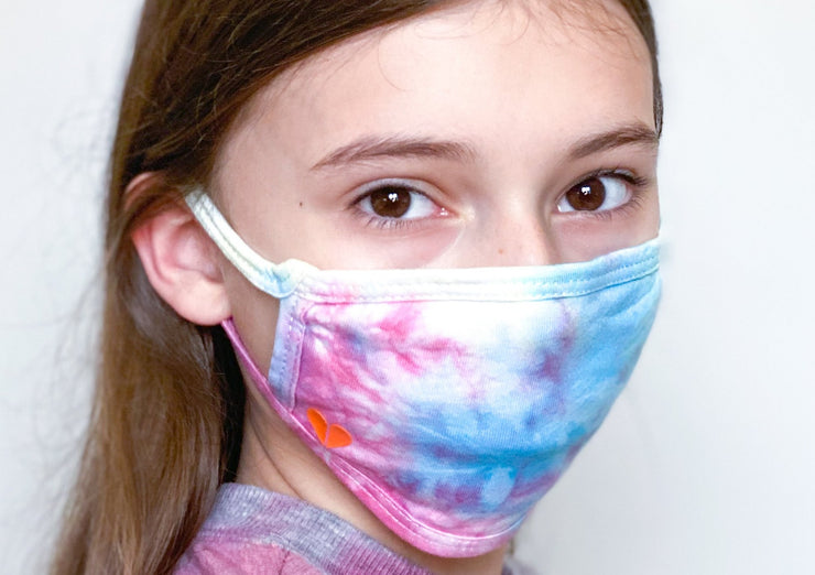 Tween girl with long hair in tie dye face mask