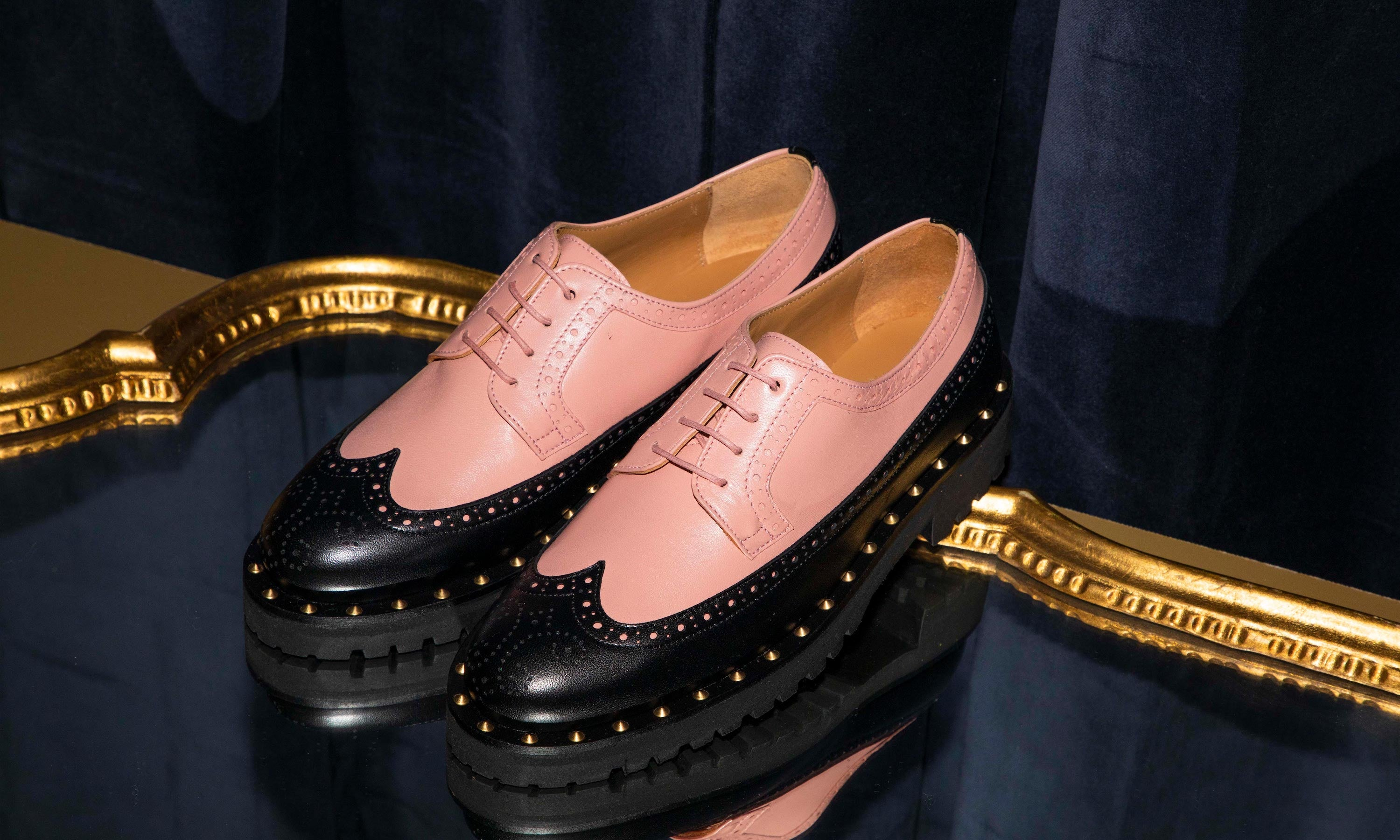Flavia our long wing derby with a soft pink upper and black wing tip sits on a lush velvet backdrop with gold detailing