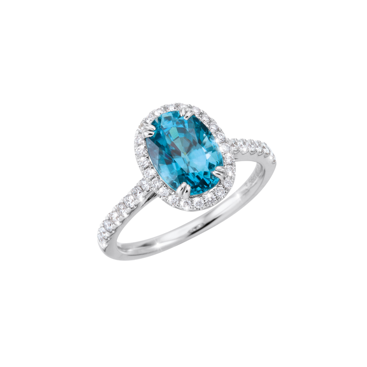 The Oliver Heemeyer Azure ring features a blue Zircon in its center, framed by a diamond set halo. The half-circle design is set with diamonds and made of 18k white gold.