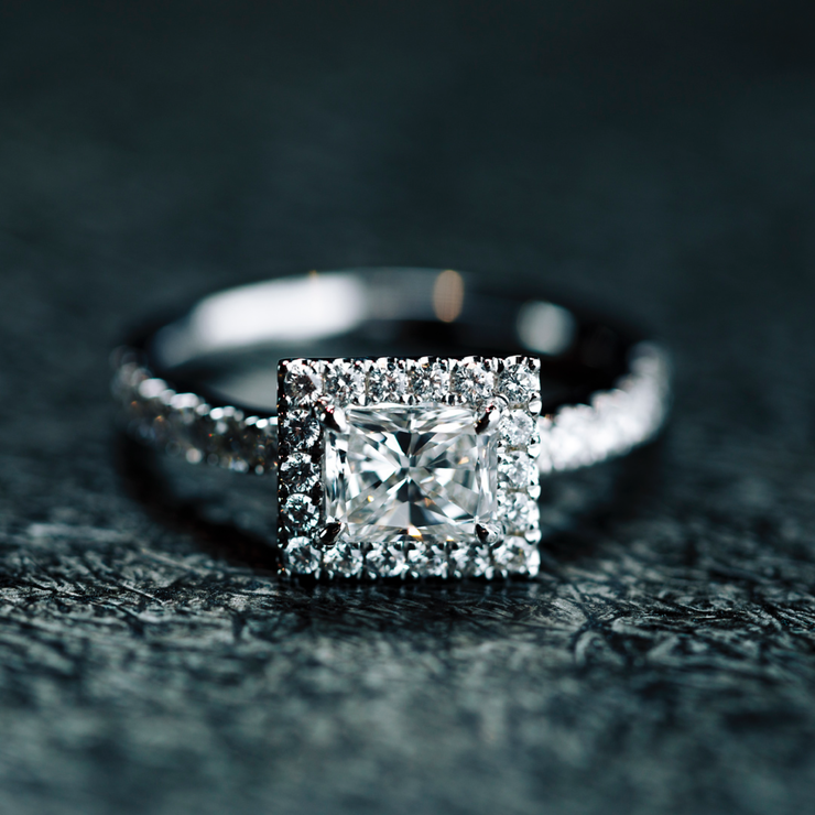 Handcrafted and made of 18k white gold, the Oliver Heemeyer Mara engagement half-circle ring features a pavé-set diamond halo that encompasses a rectangular cut center diamond.