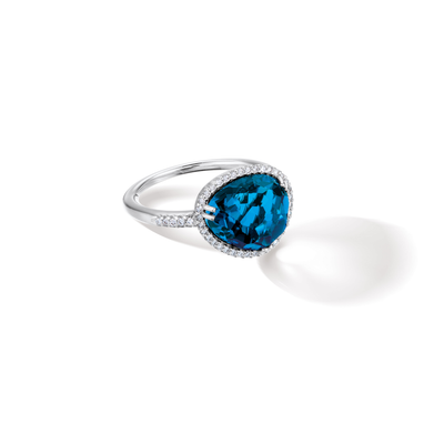 Oliver Heemeyer Cocktail diamond ring carrying a colourful topaz in its center, framed with sparkling diamonds and made of 18k white gold. Stone colour: London blue