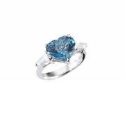Oliver Heemeyer 18k white gold ring featuring a blue heart shaped sapphire in its center, complemented by two tapered cut diamonds. A true symbol of deep love.