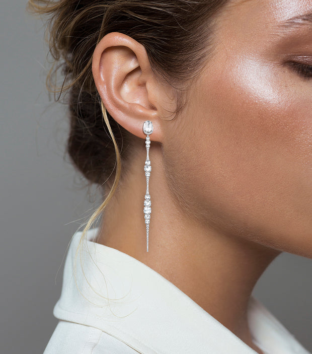 Woman wearing the Oliver Heemeyer 18k white gold Ice earrings, designed in the shape of a icicle and adorned with diamonds.