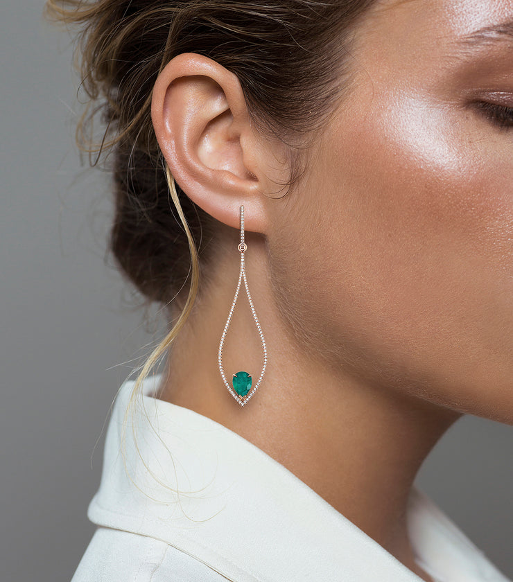 Woman wearing the Oliver Heemeyer 18k rose gold chandelier earrings, adorned with numerous diamonds and refined with two drop shaped Colombian emeralds.