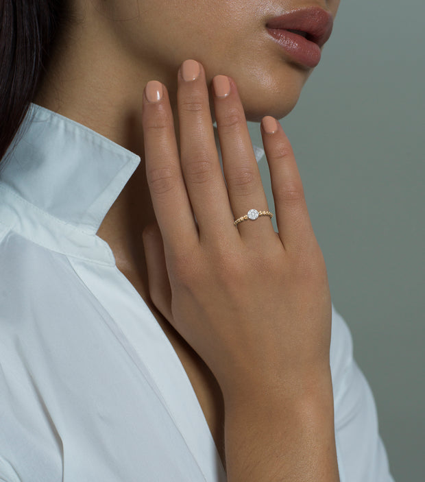 Woman wearing the Oliver Heemeyer Carmen diamond ring. Mounted on twelve 18k yellow gold beads, the seven beautiful diamond center stones make Carmen a sparkling companion.